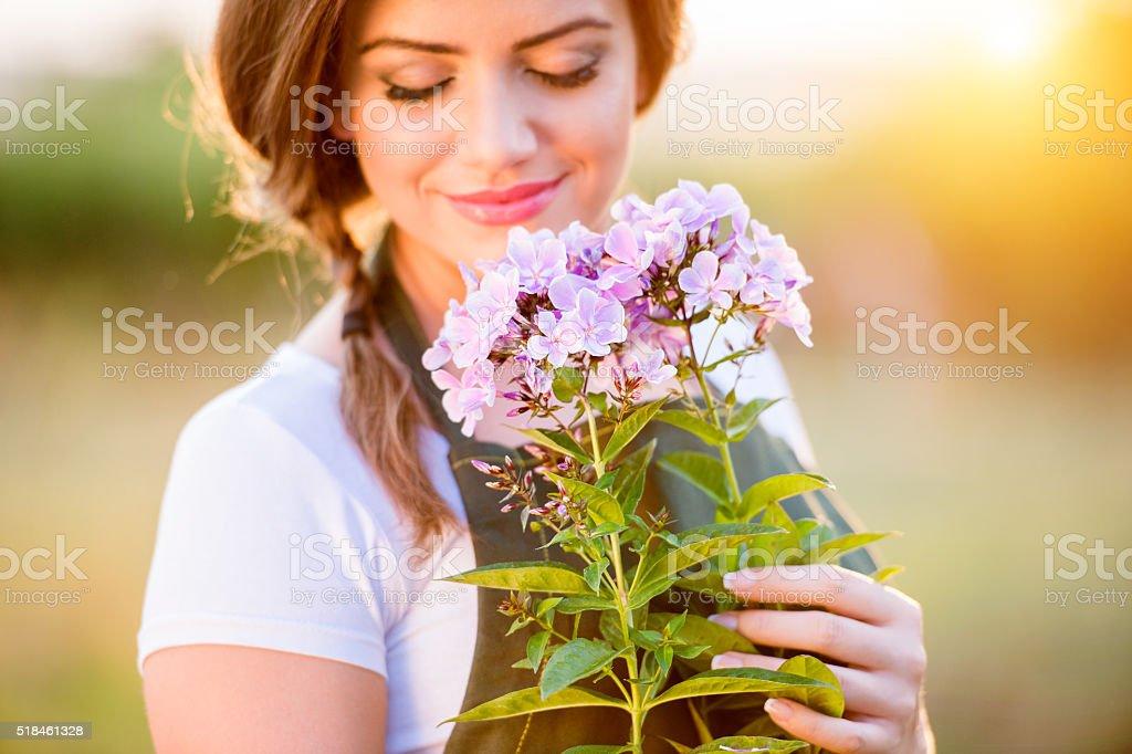 Young gardener in her garden holding flowers, sunny nature