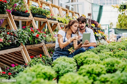 Smiling young couple working in garden center looking at a digital tablet.