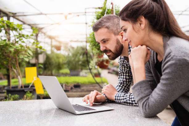 Young gardeners with laptop in a large greenhouse with pots of seedlings. stock photo