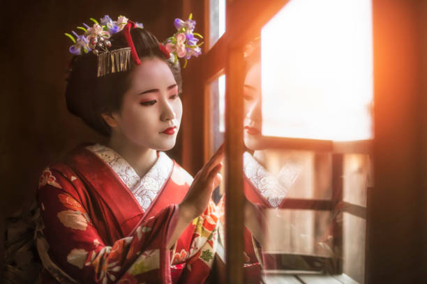 Young geisha girl looking through window stock photo
