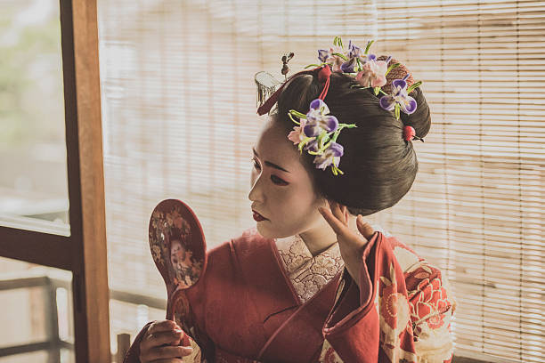 young geisha woman adjusting hairstyle with hand mirror - geisha girl stock photos and pictures