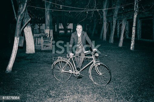 492529287istockphoto young gentleman at night with old bike 615279354