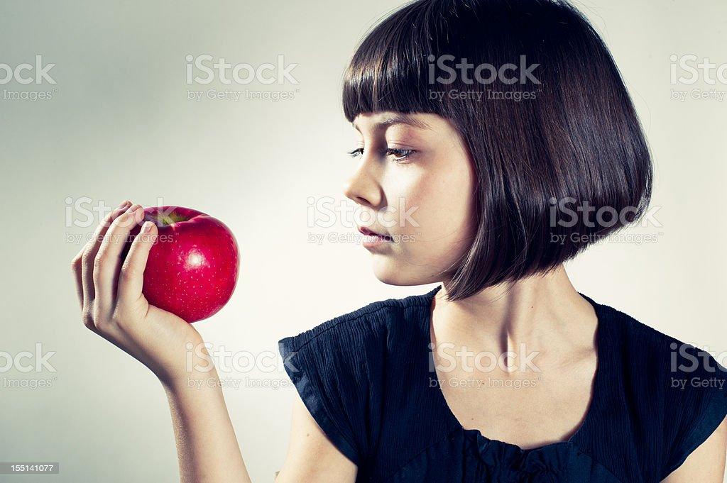 Jeune fille sur le point de manger une pomme rouge. - Photo