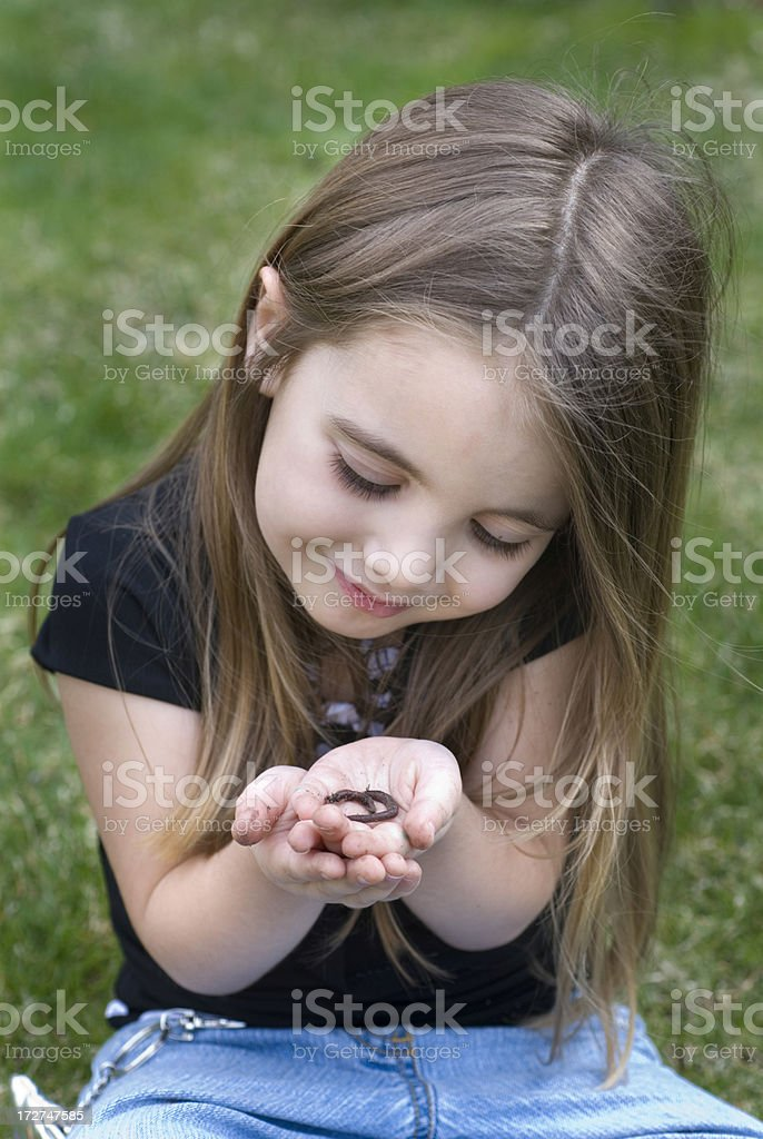 Young girl admiring her pet worm. stock photo