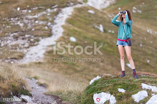 Young girl admiring the view from the mountain top using a binocular
