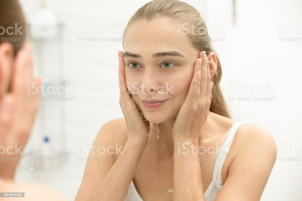 Young girl after washing her face water near the sink stock photo