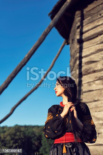Young girl among old wooden buildings