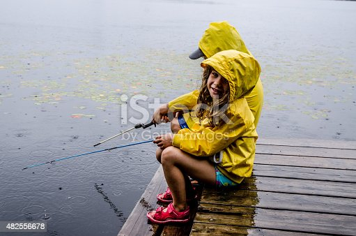 A little girl and little boy wearing a yellow raincoat are sitting on the dock and fishing in the lake Sept-Iles (Portneuf) while it's raining.