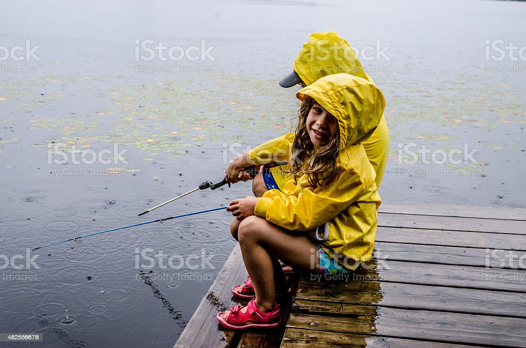 Young girl and boy fishing under rain stock photo