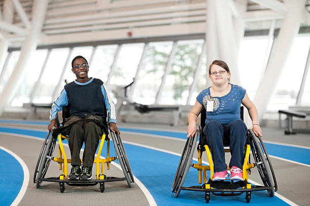 young girl and boy in their wheelchairs - wheelchair sports stock photos and pictures