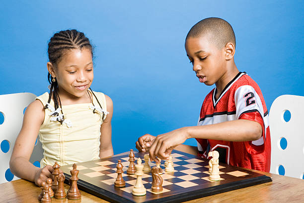 A young girl and boy playing a game of chess stock photo
