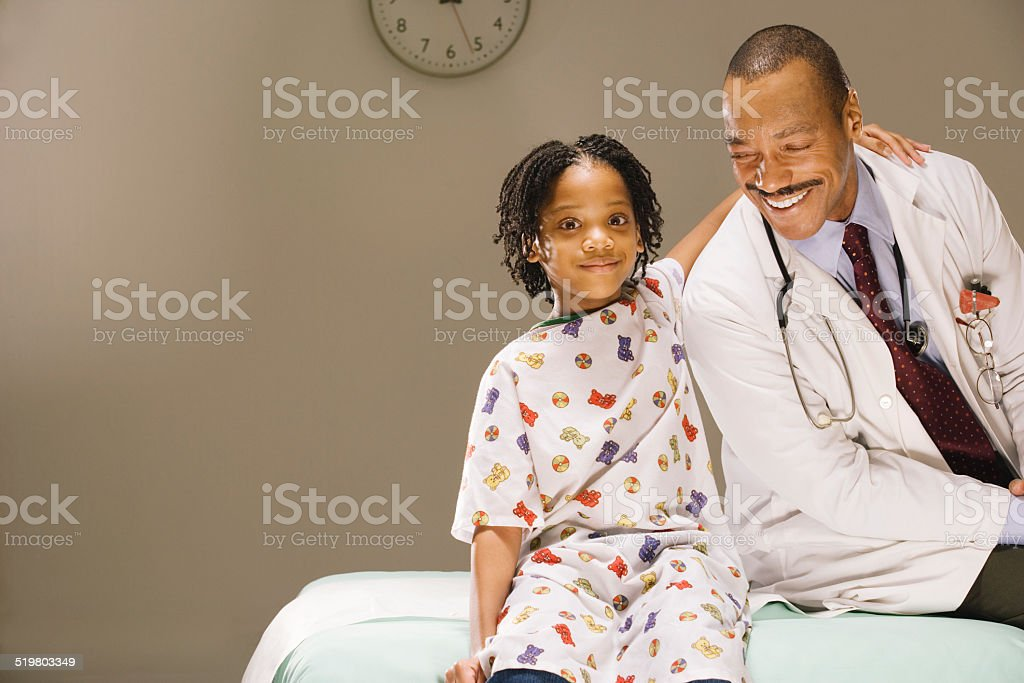 Young girl (8-9) and doctor smiling, sitting side by side stock photo