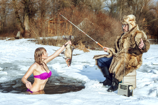 Young girl in a swimsuit stands in the ice-hole and stretches the fish to an elderly fisherman.