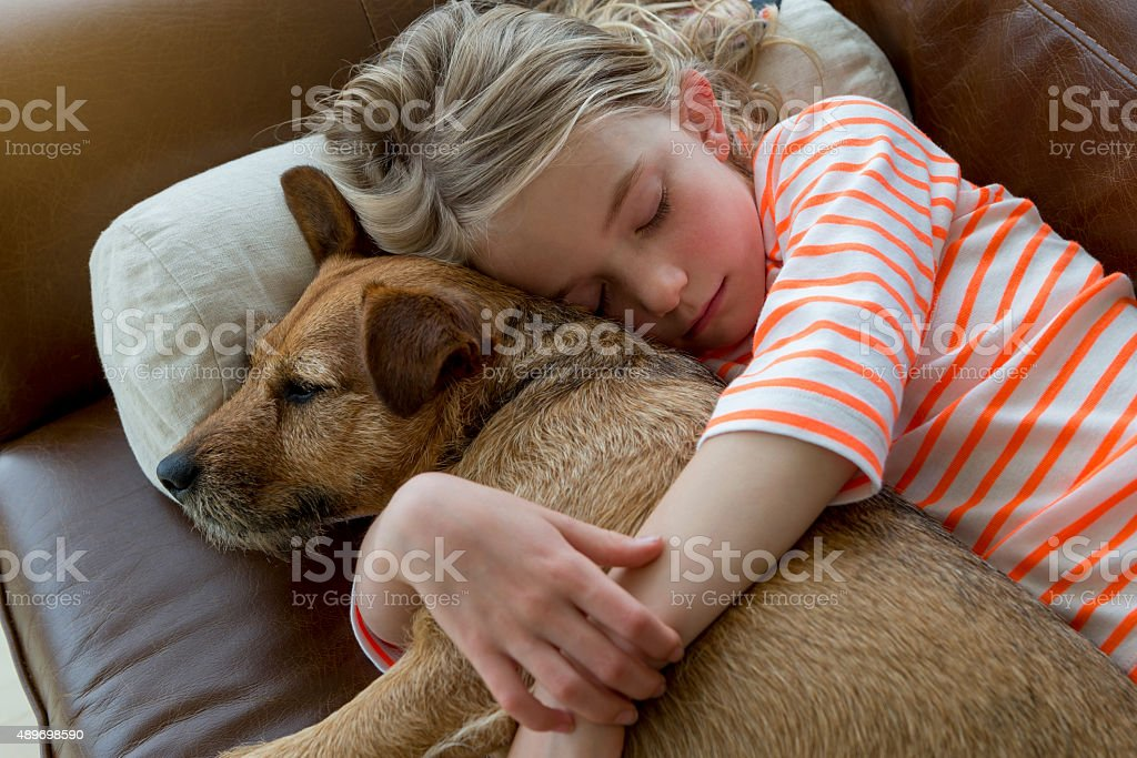 Young girl and her dog cuddling at home stock photo
