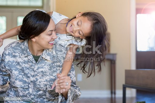 Young girl hangs on her mother who is in military uniform. They are in their living room as they play and smile with one another.