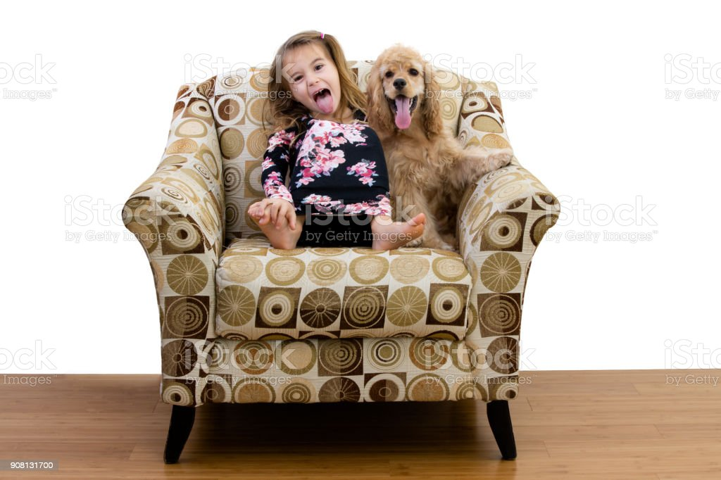 Young girl and her puppy relaxing in an armchair stock photo
