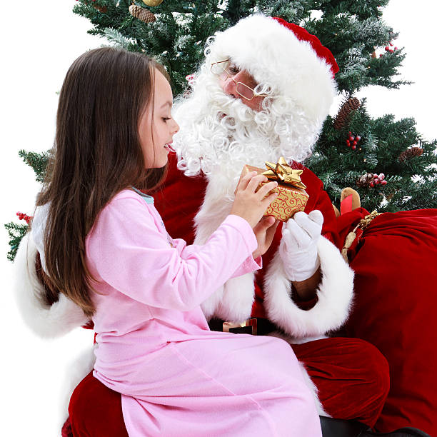 young girl and santa under christmas tree - carolinemaryan stock pictures, royalty-free photos & images