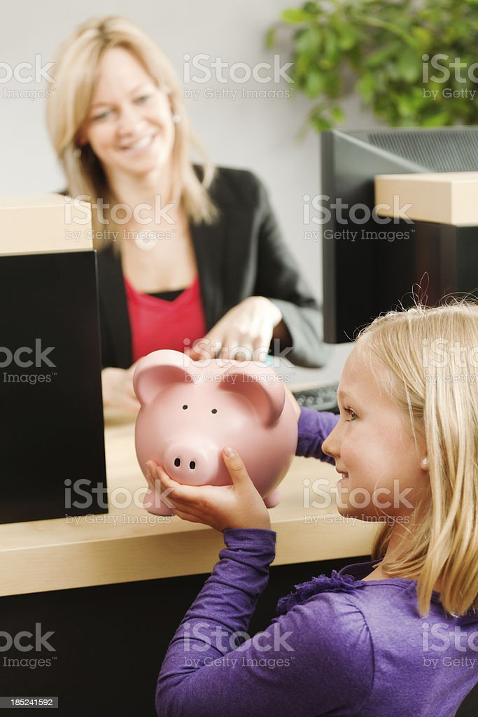 Young Girl and Saving Piggy Bank with Retail Banking Teller stock photo