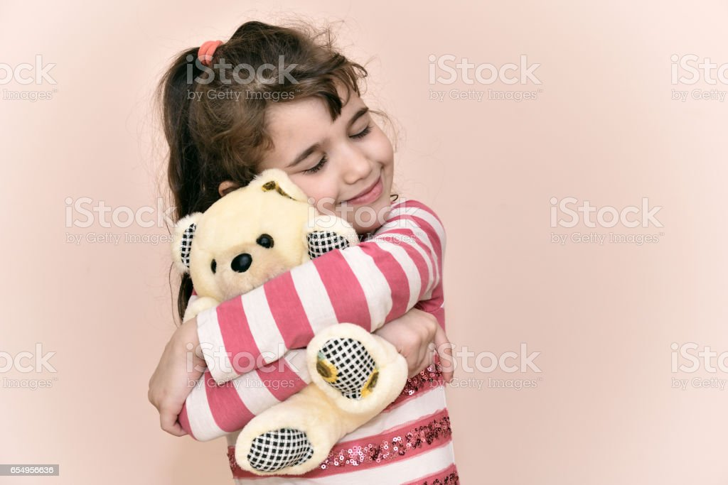 Young girl and teddy bear stock photo