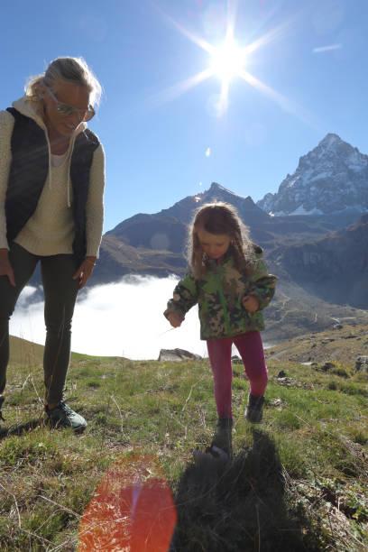 Jeune fille et femme explorent les prairies de montagne - Photo