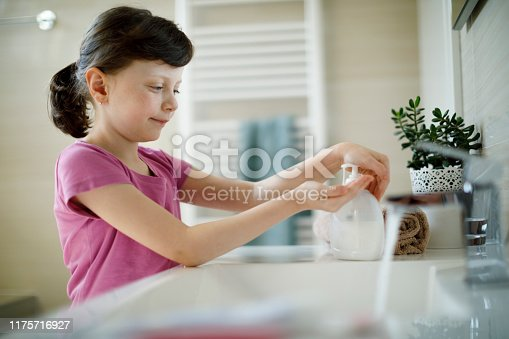 Young girl applying antiseptic hand sanitizer