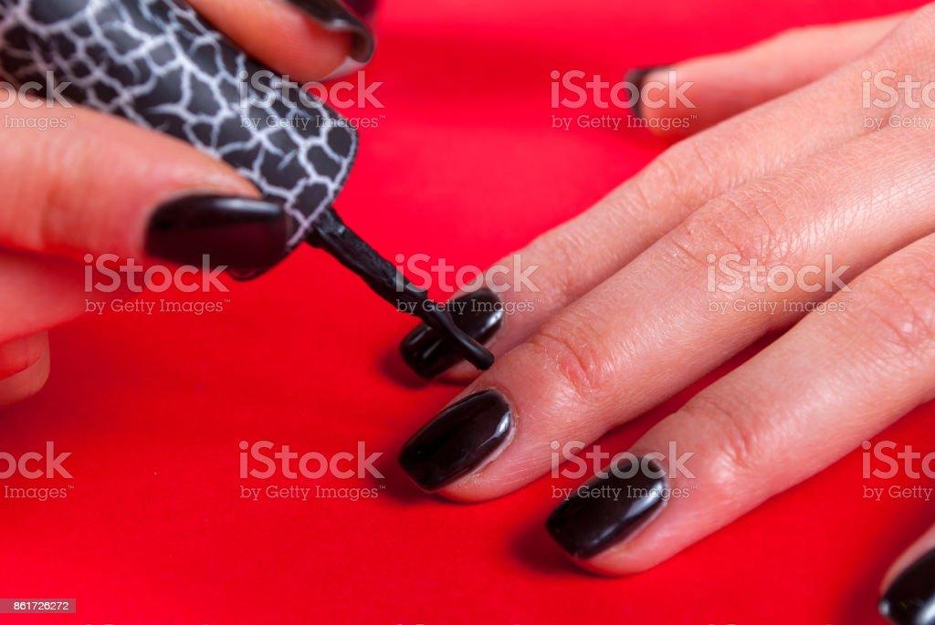 Girl applying black nail polish manicure herself with brush on...