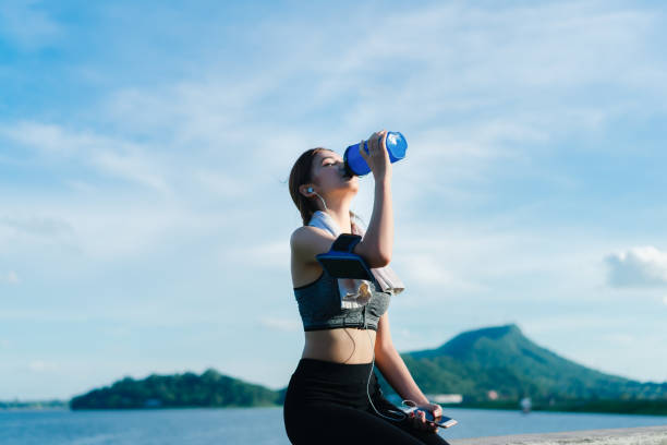 young girl asian drinking protein shake with sport bra after exercise workout outdoor at beach seascape in summer for muscle building and slim fit body nice perfect - runner rehab gym foto e immagini stock