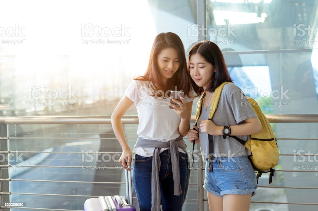Young girl asian together using mobile smartphone with carrying hold suitcase luggage and passenger for tour travel booking ticket flight in airport international vacation time in holiday relaxation. stock photo