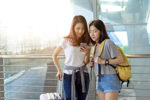 chica joven asiática con móvil smartphone con transporte mantenga maleta equipaje y pasajeros para el recorrido del tour reservar billete vuelo en tiempo de vacaciones internacionales de aeropuerto en la relajación de vacaciones. - viaje a asia fotografías e imágenes de stock