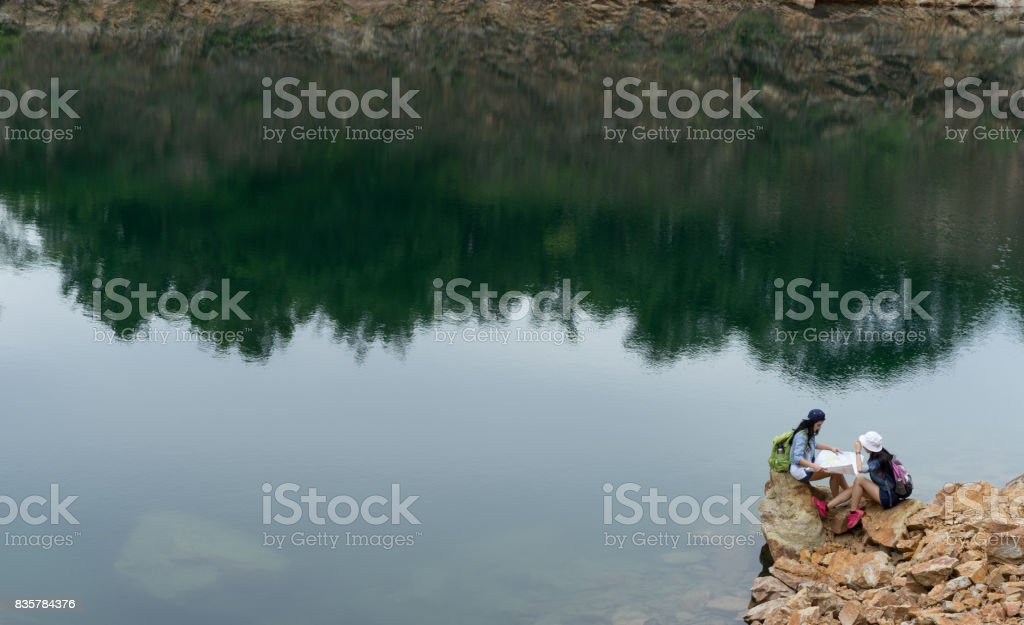 47f59edc2870 Young girl asian together with backpack sitting on big rock open maps  location travel trip in the mountain and lake - Stock image .