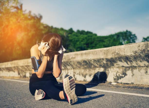 junges mädchen asiatische berührende kopf auf straße laufen training übung - mit muskelkater trainieren stock-fotos und bilder