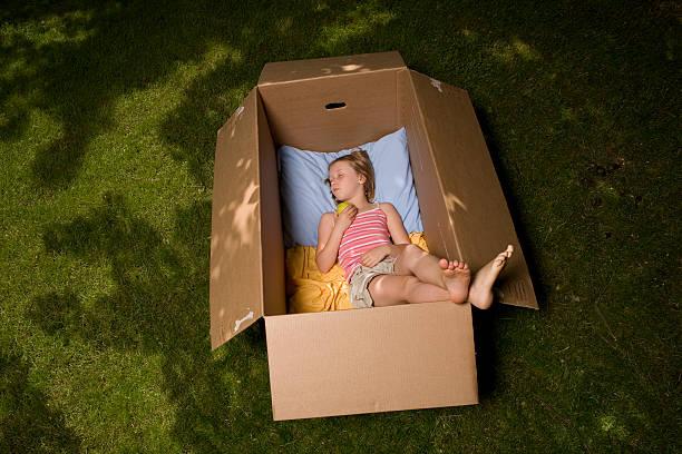 junges mädchen schlafen sie unter einem baum in brown pappkarton. - mädchen spielhaus stock-fotos und bilder