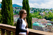 Panorama with Young Girl in sunglasses looking at Cityscape and landscape at Old city of Baden Baden of Baden Wurttemberg in Germany. View of woman at nature in Bath and spa German town in Europe.