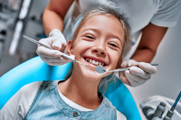 Young girl at dentist. Dentist hans with dental treatment stock photo