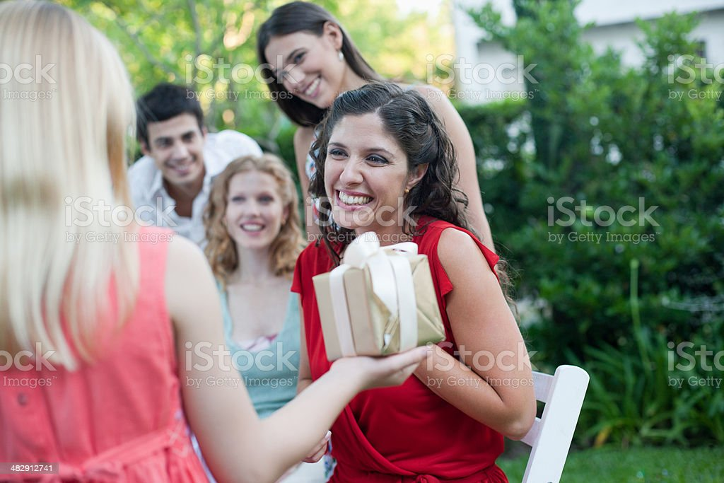 Young girl at outdoor party giving gift to woman with partygoers watching and smiling stock photo
