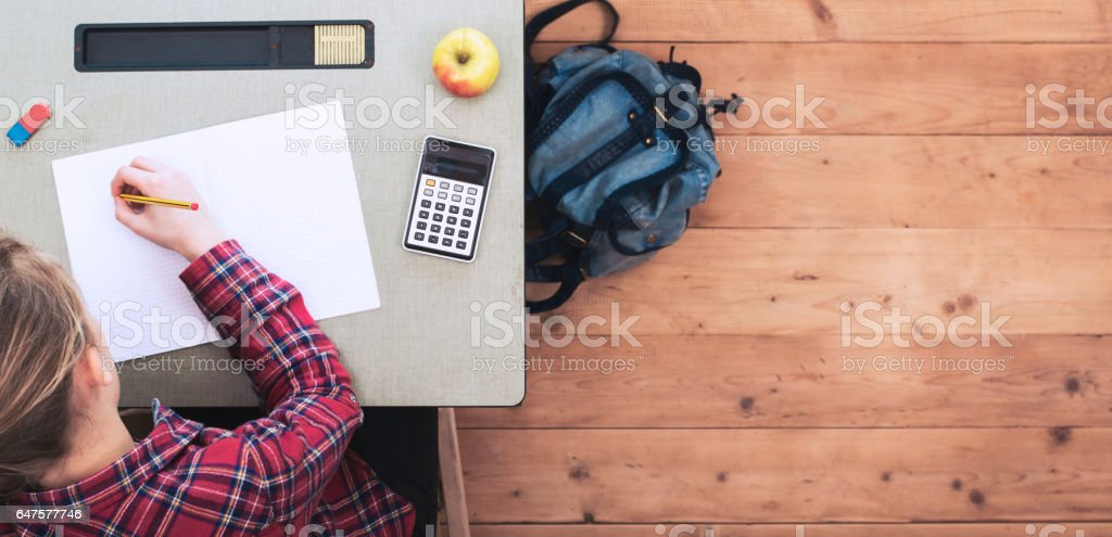 Young girl at school desk header stock photo