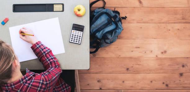 学校机ヘッダーで若い女の子 - 作文の授業 ストックフォトと画像
