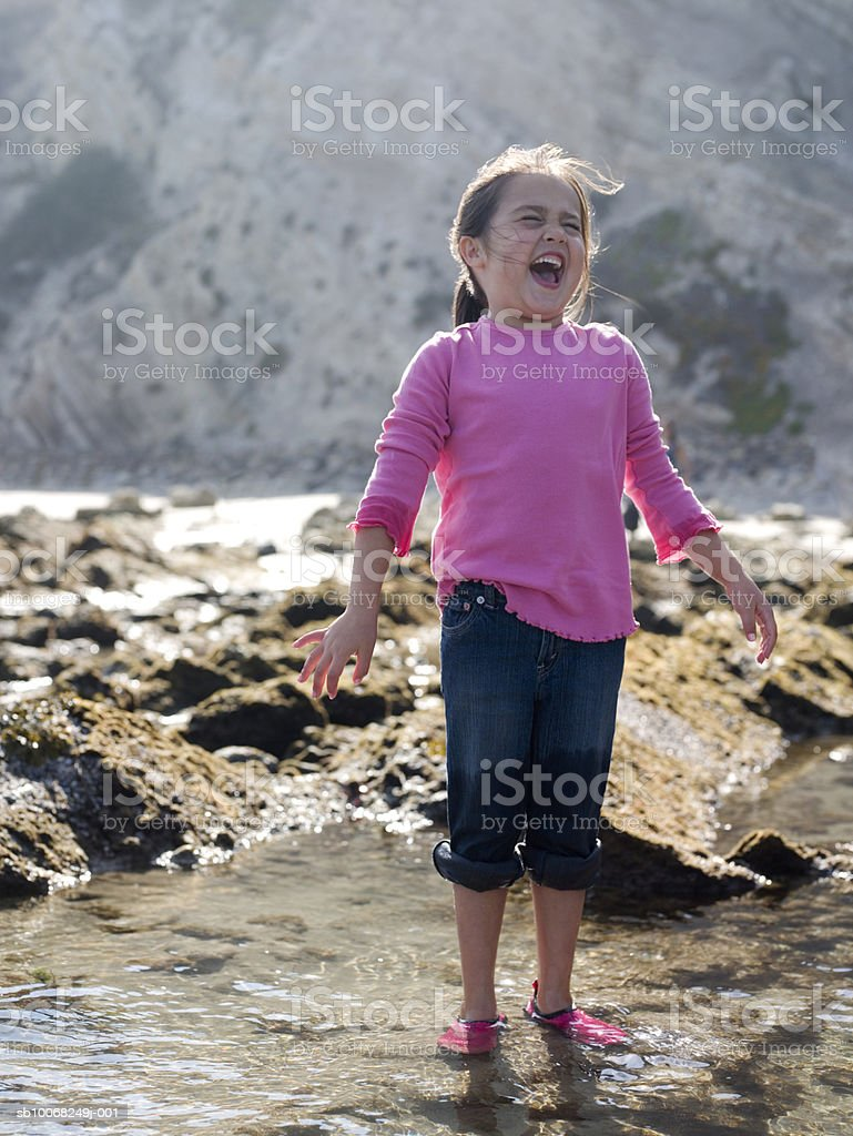 Young girl (6-7) at seashore, laughing royalty free stockfoto