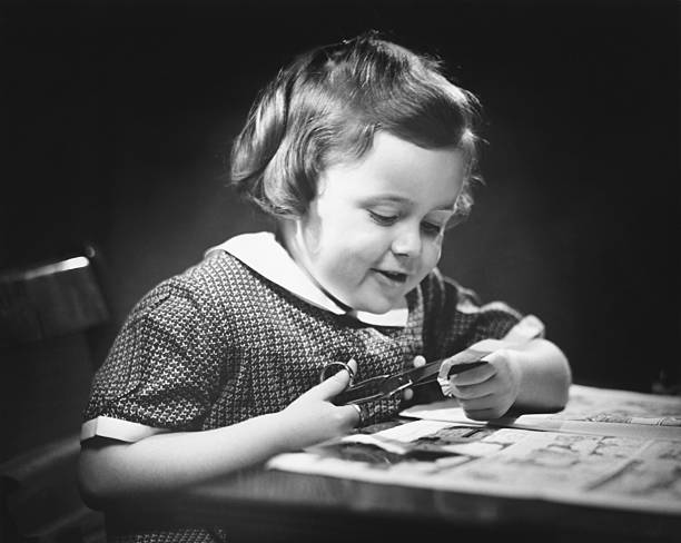 Young girl (4-5) at table cutting paper with scissors, (B&W), close-up stock photo