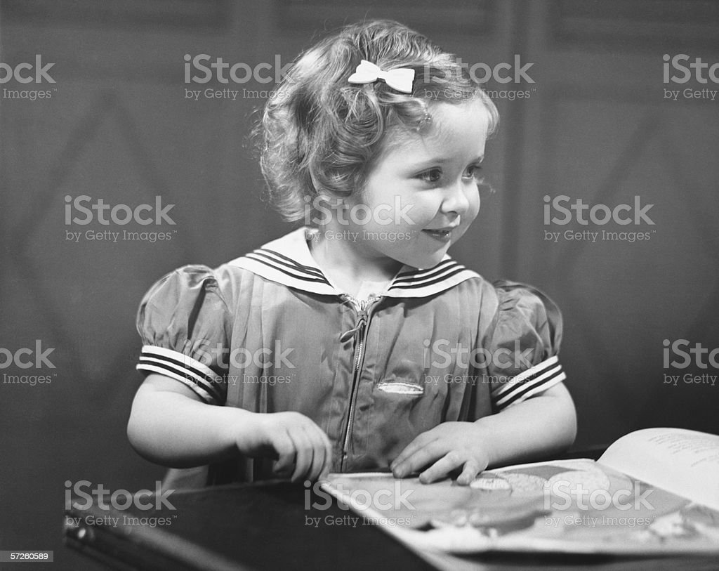 Young girl (4-5) at table reading book, (B&W) royalty-free stock photo