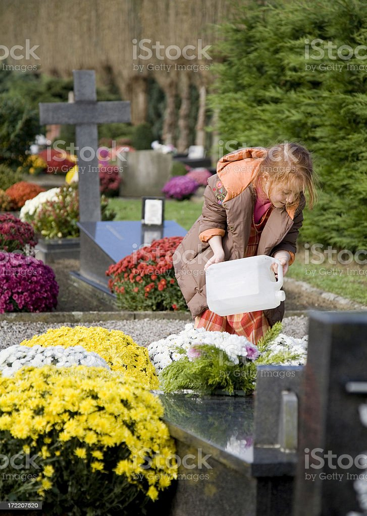 "Young girl at the graveyard, watering flowers ""Young, 6 year old girl, visiting a relative at the graveyard, watering the flowers she brought."" Absence Stock Photo"