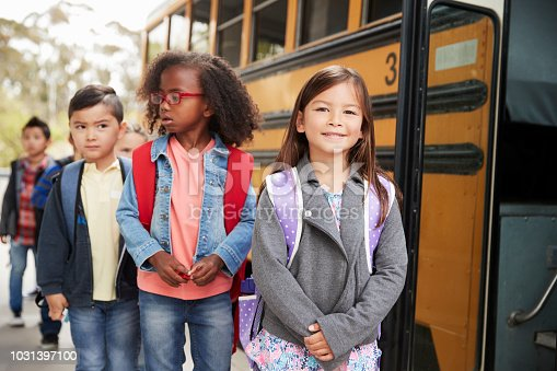 1031397608 istock photo Young girl at the head of the queue for the school bus 1031397100