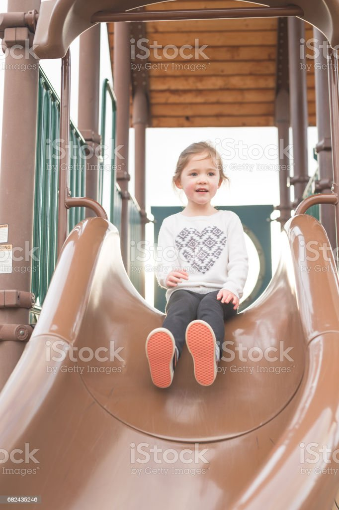 Young girl at top of slide prepares to descend royalty-free stock photo