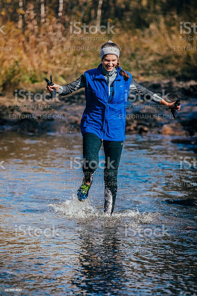 young girl athlete crossing a mountain river stock photo