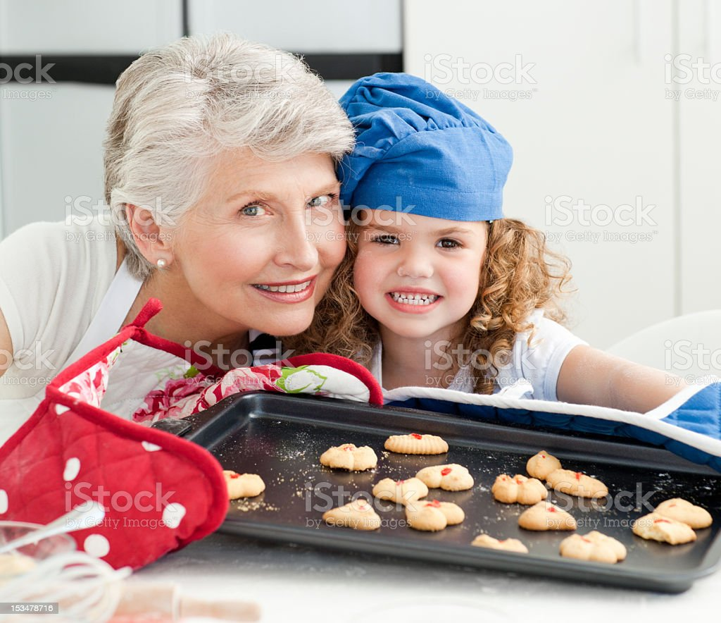 Young girl baking cookies with her grandmother royalty-free stock photo