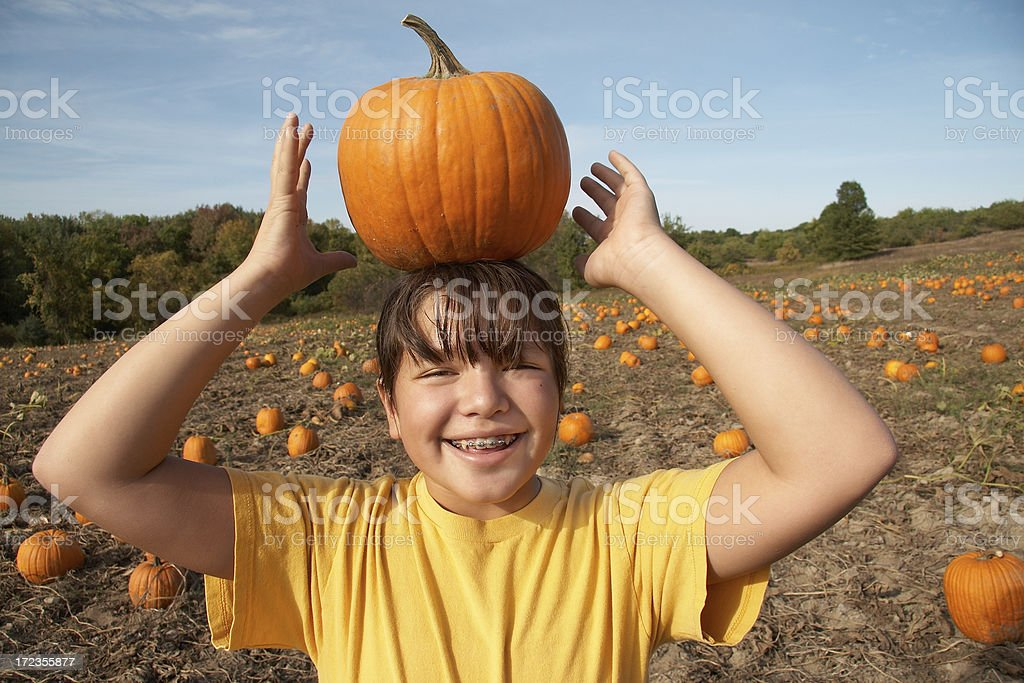 young girl balancing pumpkin on her head royalty-free stock photo