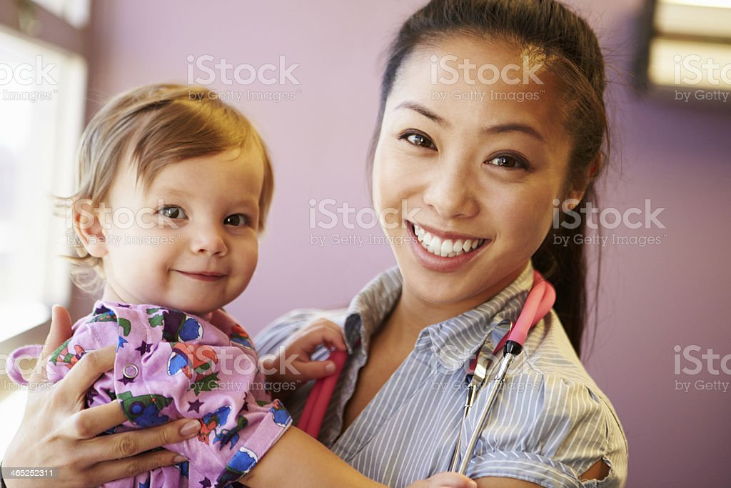 Young Girl Being Held By Female Pediatric Doctor stock photo