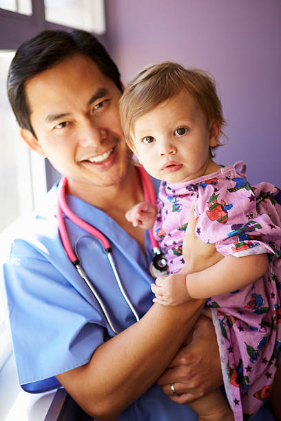 Young Girl Being Held By Male Pediatric Nurse stock photo