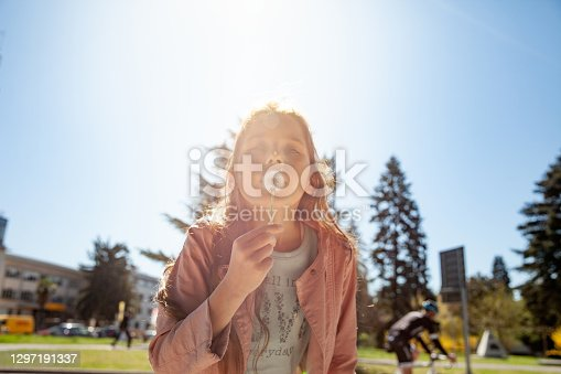 Young Girl Blowing a Dandelion in Public Park.