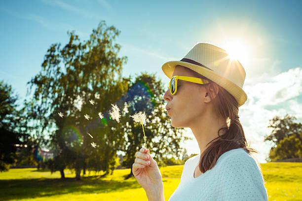 young girl blowing dandelion flower in the park. - bonne chance photos et images de collection